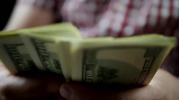 Hands Zählen US-Dollar-Scheine im Dunkeln