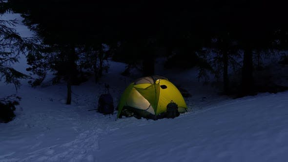 Yellow Iluminated Tent in Winter Forest