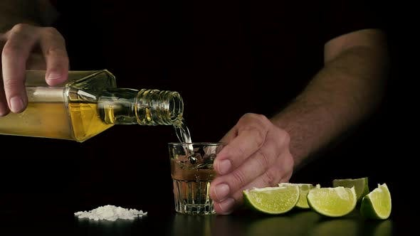 Thumbnail for The Barman Holds a Shot and Pours Tequila