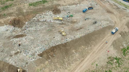 Top View on Garbage Trucks Unload Garbage to a Landfill