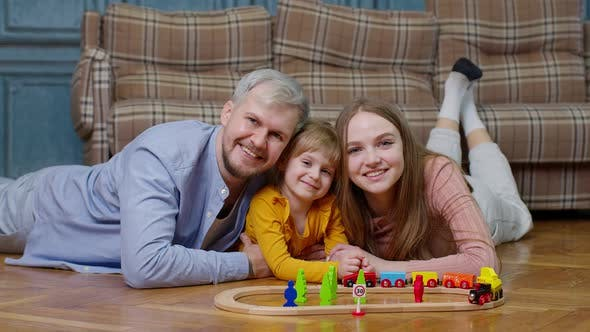 Family of Mother Father with Daughter Child Girl Riding Toy Train on Wooden Railway at Home Room