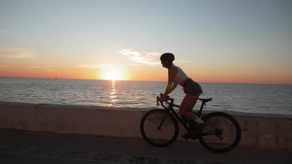 Thumbnail for Young female is cycling on bicycle along sea promenade at sunrise. Woman cycling outdoors