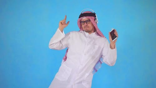 Arab Man in Headphones Stands on a Blue Background and Vigorously Dancing To the Music
