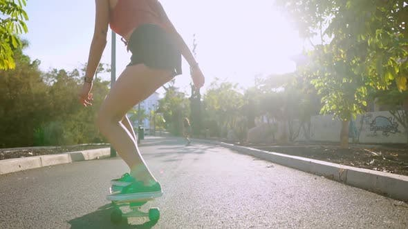 Thumbnail for Girl in Slow Motion Rides a Skateboard in the Park with Palm Trees
