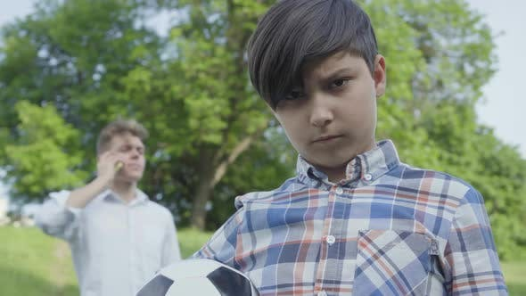 Thumbnail for Portrait of a Sad Boy Looking Into the Camera Holding the Soccer Ball in the Foreground. The Young