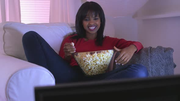 Thumbnail for Black girl watching funny movie at home