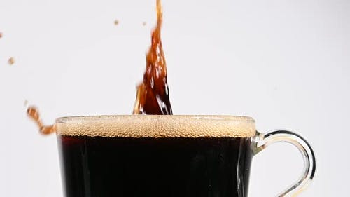 Werfen braune Zuckerwürfel in Tasse schwarzen Kaffee