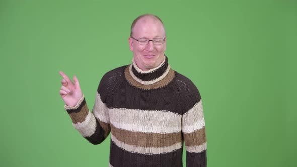 Thumbnail for Happy Mature Bald Man with Turtleneck Sweater Laughing While Pointing Finger