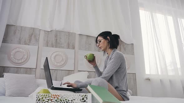 Thumbnail for Cheerful Girl in Eyeglasses Typing on Laptop Computer