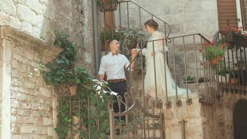Romantic wedding couple standing on the stair in old town in Montenegro.