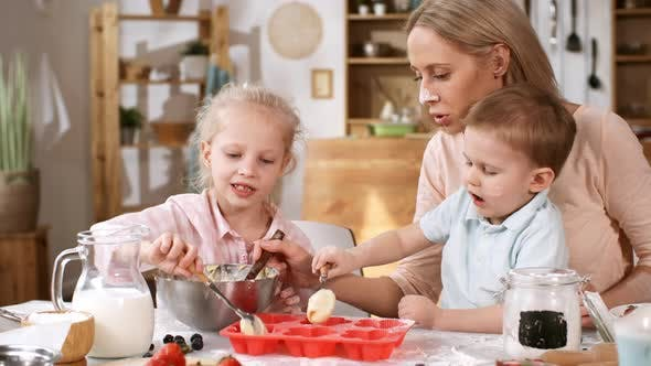 Caucasian Mum with Kids Filling Baking Mold with Batter