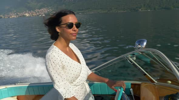 A woman on a classic luxury wooden runabout boat on an Italian lake