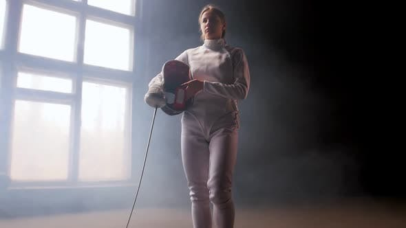 Cover Image for A Young Pretty Woman Fencer Putting on a Protective Helmet and Gets Into Position