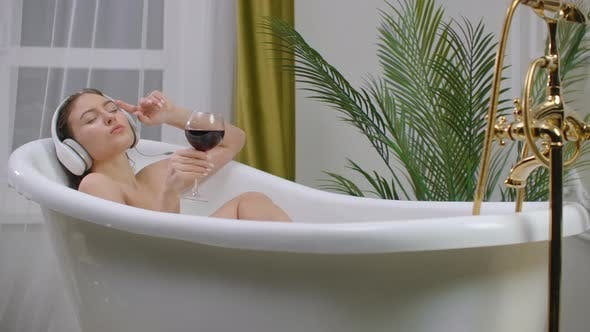 Beautiful Young Woman Enjoying Pleasant Bath with Foam, Holding a Glass of Wine, Woman Listening To Music