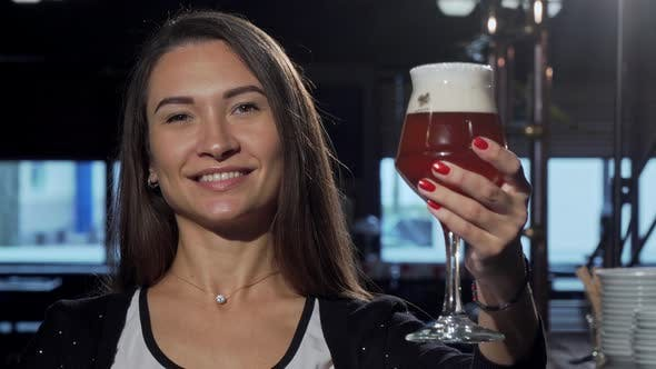 Thumbnail for Gorgeous Happy Woman Smiling, Holding Out Her Beer To the Camera