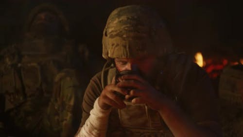 Depressed Soldier Drinking Near Fire at Night