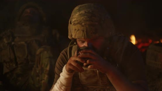 Thumbnail for Depressed Soldier Drinking Near Fire at Night