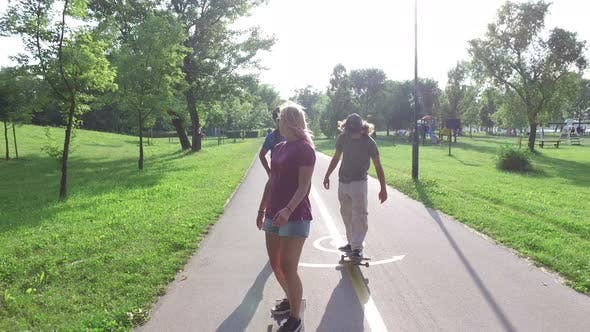 Thumbnail for Cool young friends skateboarding on sunny day
