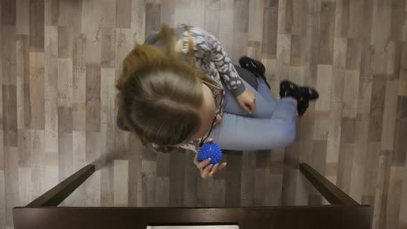 Girl Spinning on Office Chair with Antistress Ball