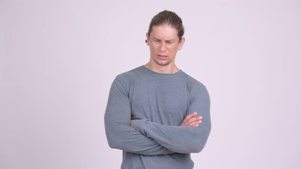 Thumbnail for Angry Man Looking Furious with Arms Crossed Against White Background