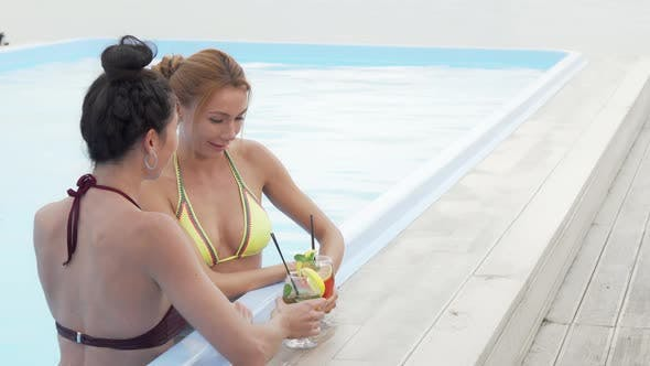 Beautiful Woman Talking While Having Cocktail with Her Friend at the Swimming Pool