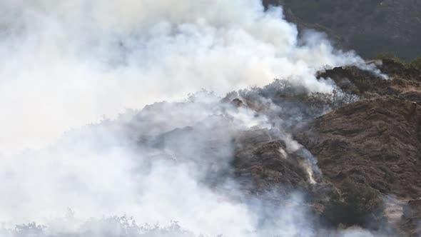 Smoke surrounding rocky mountainside during wildfire