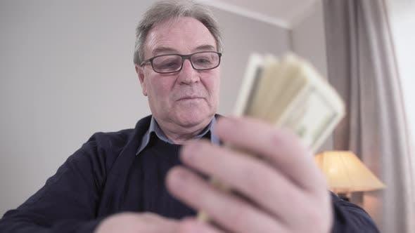Thumbnail for Cash Fan Putting in Bunch, Senior Caucasian Man in Eyeglasses Smiling. Portrait of Rich Retiree