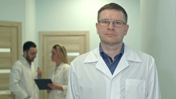 Thumbnail for Male Doctor Looking at Camera While Medical Staff Working on the Background