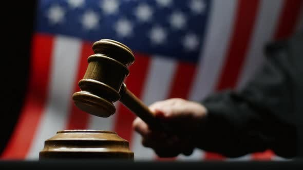 Thumbnail for Judge With Hammer In His Hand Against Waving American Flag In United States Court Room