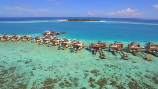 Aerial drone view of scenic tropical island and resort hotel with overwater bungalows in Maldives.