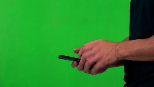 Thumbnail for Young Man Works on Smartphone (Typing) - Green Screen - Studio - Closeup