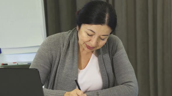 Thumbnail for Senior Business Woman Taking Notes While Working on the Laptop