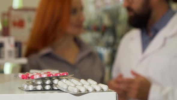 Thumbnail for Pharmacist Taking Blister of Pills From the Counter, Talking To His Female Customer