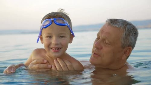 Child and grandfather bathing in the sea