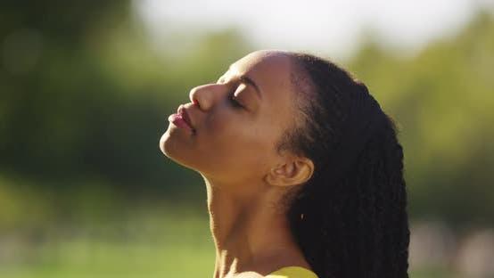 Thumbnail for Black woman feeling the sun shine on her face