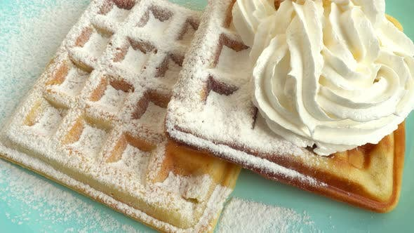 Preparation of waffles. Whipped cream is applied to the waffles.