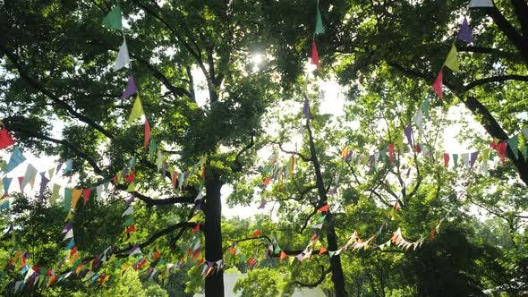Thumbnail for Colorful Flags Hanging on Branches of Trees As Festive Decoration for Outdoor Party. Bright Summer