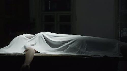 Leiche mit einem weißen Tuch in der Dunkelkammer bedeckt