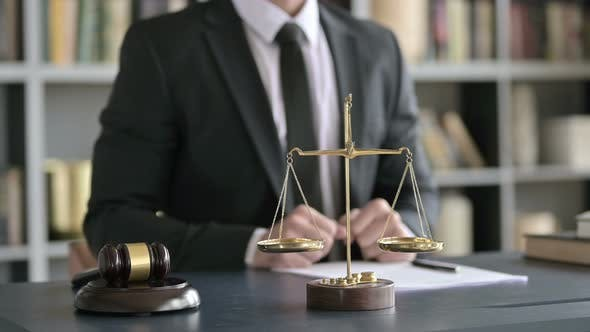Thumbnail for Close Up of Balance Scale and Gravel on Table with Lawyer