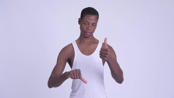 Cover Image for Young Confused African Man Choosing Between Thumbs Up and Thumbs Down