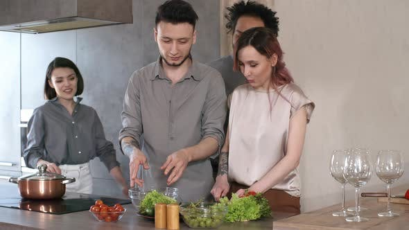 Cover Image for Happy Couple Cooking Dinner and Greeting Friends at Home