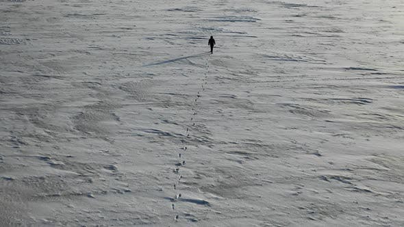 Thumbnail for Aerial View of a Human with Heavy Backpack Walking By Snow Desert in Alaska