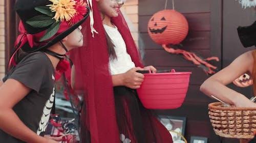 Glückliche Frau gibt Süßigkeiten an Kinder an Halloween