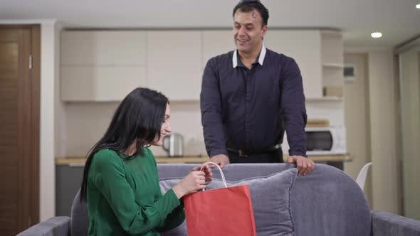 Smiling Wealthy Middle Eastern Man Giving Gift to Surprised Excited Caucasian Woman Sitting on Couch