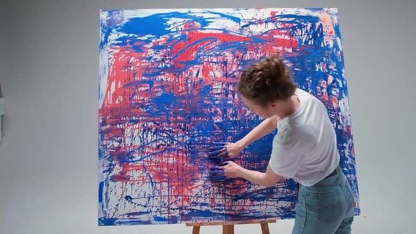 Modern Art Young Female Artist Draws with Her Hands on a Large Canvas in a White Room a Talented