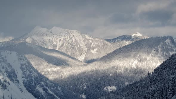 Rolling Cloud Shadows Time Lapse On Snow Covered Mountain Hills With Thick Forest Trees