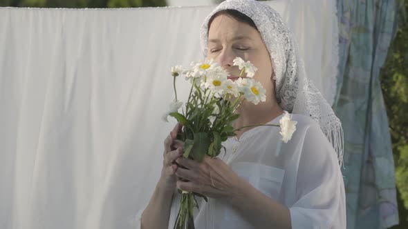 Thumbnail for Portrait Senior Woman with White Shawl on Her Head Sniffing Daisies Looking at Camera Near