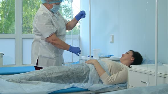 Thumbnail for Nurse in Gloves and Mask Putting Female Patient on a Drip in a Hospital Ward