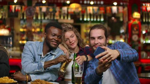 African American with European Friends Sitting in a Bar Takes a Selfie