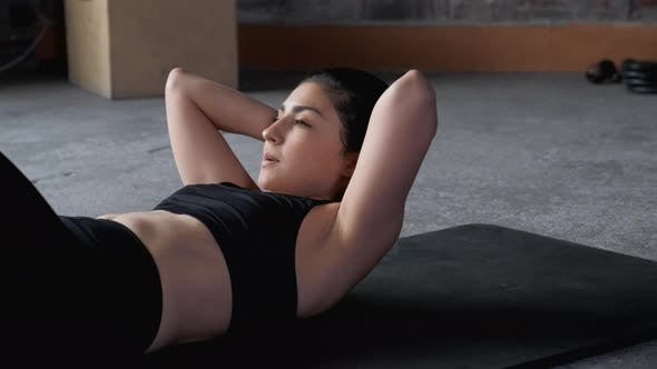 Close-Up Athletic girl in sportswear is pumping the abdominals. Sporty woman is doing abs